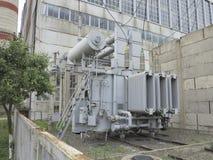 Trasformatore elettrico ad alta tensione industriale enorme della sottostazione sui rai Fotografia Stock