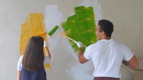 Trasformazione e rinnovamento domestici: giovani coppie felici che dipingono i loro interni della nuova casa facendo uso dei rull archivi video