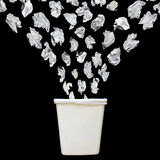 Trash. Bunch of cumbled paper being throwing into a trash bin or waste bin isolated on black background royalty free stock photo