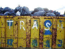Trash. An old, weathered trash bin filled with bags of garbage Royalty Free Stock Photos