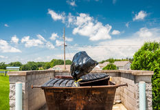 Trash bag being thrown in the air into a dumpster Royalty Free Stock Photography