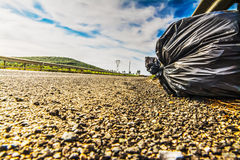 Trash bag on the ege of the road Royalty Free Stock Photos