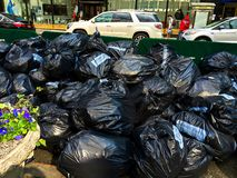 Trash bags stored prior to truck pickup. Filled trash bags wait in Bryant Park NYC for trash trucks to remove them royalty free stock images