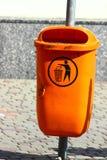Trash basket. On the street on the sidewalk stands damaged trash basket orange Royalty Free Stock Photos