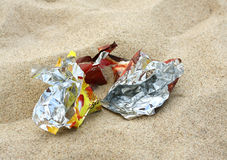 Trash on the beach. Crumpled foil package on the beach Stock Photography
