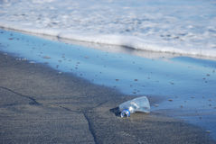 Trash on the beach. Plastic water bottle being washed up on the beach. plastic bottles and other items kill marine life stock photography