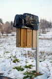 Trash bin. A wood trash bin with black plastic bag,winter Stock Image