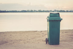 A trash bin on the beach. A green trash bin on the beach Royalty Free Stock Images