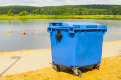 Trash bin. Trash bin in blue, standing in park in the background of beach Royalty Free Stock Images