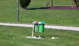 Trash bin full in an outdoor park Royalty Free Stock Image