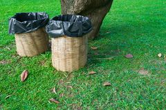 Trash bin made of bamboo baskets on green grass stock images