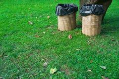 Trash bin made of bamboo baskets on green grass stock photo