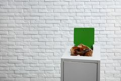 Trash bin with paper and cardboard near brick wall, space for text. Recycling concept stock photo