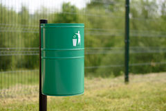 Trash bin in the park. A green metal trash bin in the park or outside of a public utility building stock photo