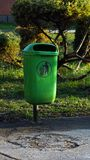 Trash bin in the park. A green plasticl trash bin in the park or outside of a public utility building royalty free stock images