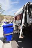 Trash Bin Pick Up. Garbage truck makes a stop to pick the trash bin Royalty Free Stock Images