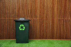 Trash bin with recycling symbol near wooden wall. Space for text. Trash bin with recycling symbol near wooden wall indoors. Space for text royalty free stock photos