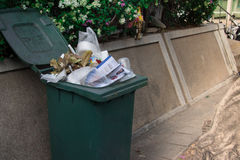 Trash bin on the sidewalk overflowing with waste and ready to be Royalty Free Stock Photos