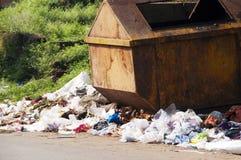 Trash bin with trash around it Royalty Free Stock Photos