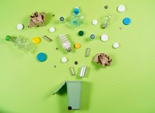Trash bins and assorted garbage isolated on green, recycle concept,. Top view stock photography