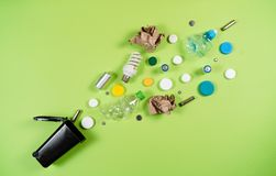 Trash bins and assorted garbage isolated on green, recycle concept. Top view stock photos