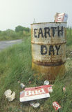Trash can. Cardboard beer cartons on the ground next to a trash can with the words �Earth Day� painted on its side Stock Photos