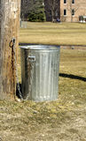 Trash Can. A metal trash can chained to a tree in a park Royalty Free Stock Image