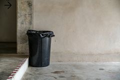 Trash can. Black Trash can on concrete wall background Royalty Free Stock Photography