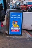 Trash can on a city street that has a sign on it`s side saying to slow down and put phone down. Philadelphia, Pennsylvania - February 5, 2019: This trash can was stock images