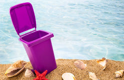 Trash can on clean sand and shells Royalty Free Stock Images