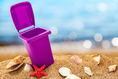 Trash can on clean sand and shells Stock Images