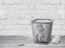 A trash can with crumpled papers stands on the floor against a white brick wall Stock Photos