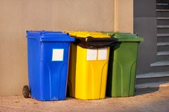 Trash can, garbage bin, recycling bin in tourist complex resort, waiting to be picked up by garbage truck. Blue, yellow and green. Trash can, garbage bin stock photo