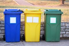 Trash can, garbage bin, recycling bin in tourist complex resort, waiting to be picked up by garbage truck. Blue, yellow and green. Trash can, garbage bin stock photography