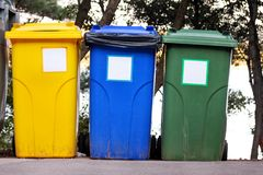 Trash can, garbage bin, recycling bin in tourist complex resort, waiting to be picked up by garbage truck. Blue, yellow and green. Trash can, garbage bin royalty free stock photos