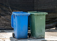 Trash can. Green and blue Trash can on concrete floor Royalty Free Stock Photos