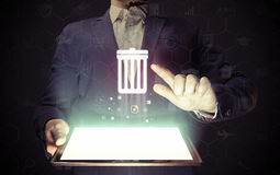 Trash can icon. Image of a manl with tablet in his hands. He presses trash can icon. The concept of deleting files, contacts, putting in order, cleaning service royalty free stock photos