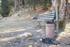 Trash can in a park with a bench, trash and charcoal. Composition Stock Images
