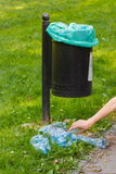 Trash can in park and heap of plastic bottles, littering of environmental Stock Photo
