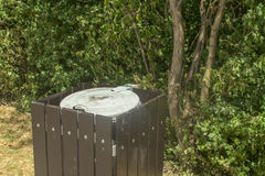 Trash can in the park surrounded by trees Royalty Free Stock Photo