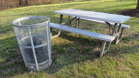 Trash Can & Picnic Table. A metal trash can next to an empty picnic table at a parkn Royalty Free Stock Photos