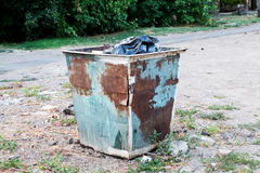 Trash can standing outdoors. Trash dumpster in ghetto neigborhoo Stock Images