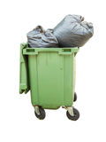 Trash can surrounded by a bunch of garbage bags isolated on whit Stock Images