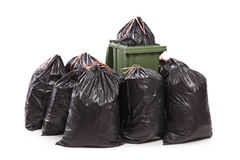 Trash can surrounded by a bunch of garbage bags Royalty Free Stock Photos