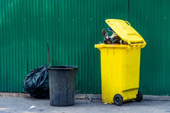 Trash can. Yellow and black plastic Trash can with green metal sheet fence on concrete road Stock Photography