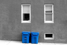 Trash Cans. This is a picture of a couple of blue trash cans against a B&W background out by the curb on trash day Royalty Free Stock Photography