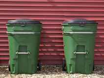 Trash Cans. Two trash cans are symmetrically placed against a red background royalty free stock image