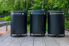Trash containers on city street. Colorful metal containers in a row for separate garbage trash collection. With signs Royalty Free Stock Photo