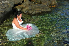 Trash the dress - beautiful bride in crystal clear sea water Stock Photography