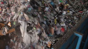 Trash in a Dumpster Waiting to be Recycled (1 of 6). Recyclables getting pushed into the beginning of the recycle plant line stock footage
